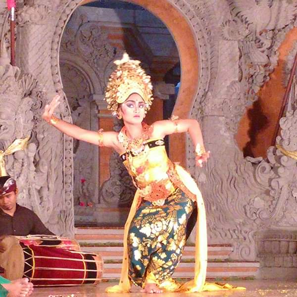 a woman doing traditional balinese dance wearing traditional gold clothing