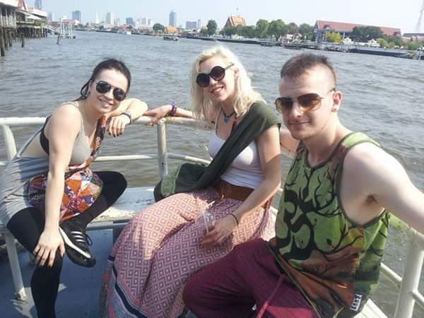 three friends on a boat in bangkok