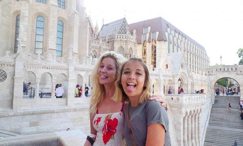 two girls sticking their tongues out at fisherman's bastion, budapest