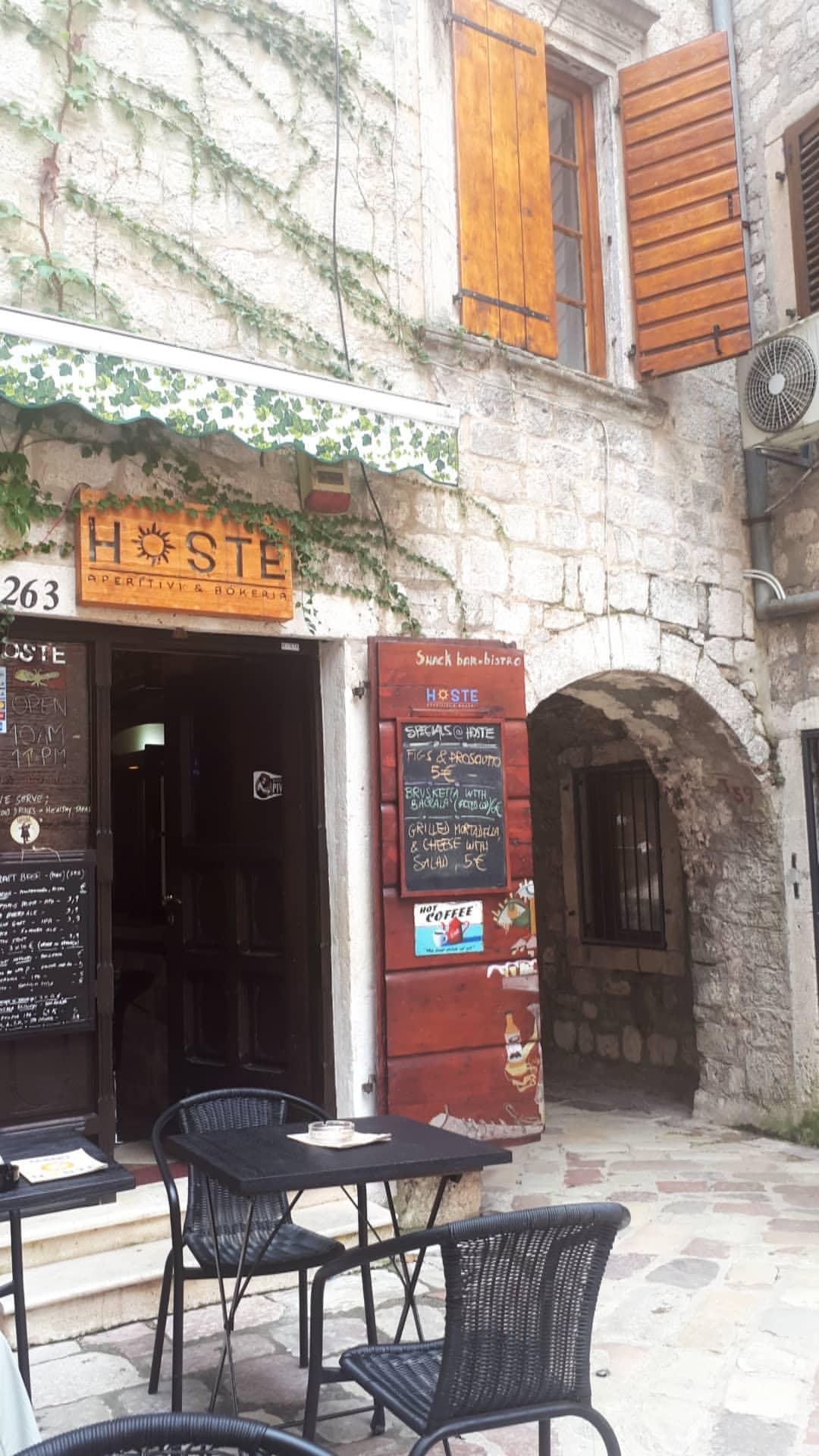 hoste kotor - a restaurant in an old town with black tables and chairs outside and ivy climbing up the walls