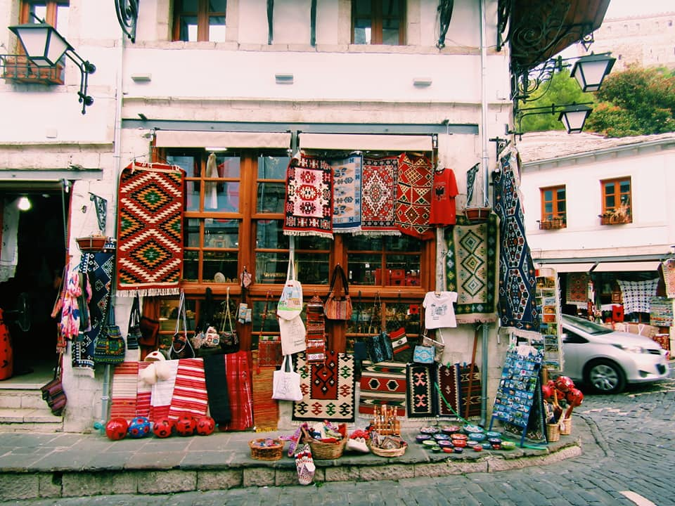 a shop on the corner of a cobbled street in Gjirokaster selling handwoven rugs and traditional Albanian clothing and souvenirs