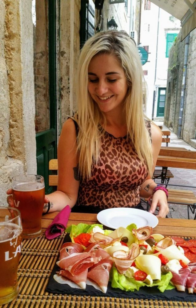 a blonde girl sitting at a table in Montenegro with a plate of cold meats and cheeses