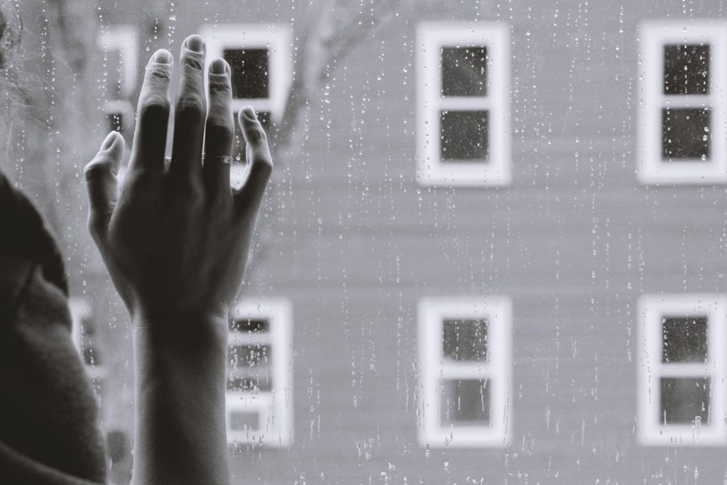black and white photo of a hand touching a windowpane overlooking an apartment block. there is rain on the window