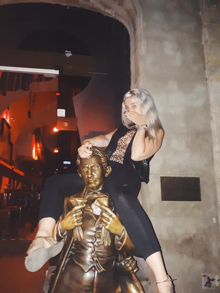 girl posing on a statue of Sacher von Masoch at Masoch Cafe Lviv