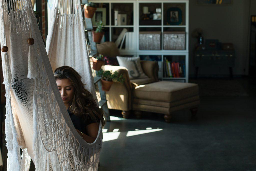 a girl reading on an indoor hammock